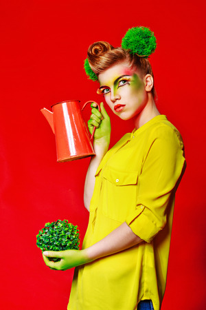 merrymaking: Cheerful girl with make-up holding a broccoli broccoli and watering. Concept of healthy food and organic products. Stock Photo