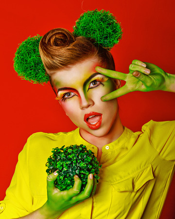 merrymaking: Cheerful girl with make-up holding a broccoli broccoli. Concept of healthy food and organic products.