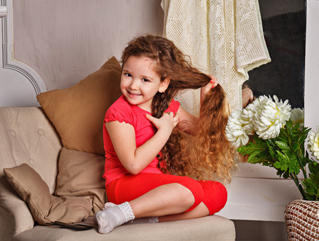Portrait of a little girl with long curly hair brushing her hair