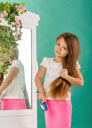 caring for: Little girl with long curly hair and comb in the hands of caring for her hair Stock Photo