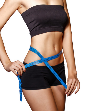 Fit and healthy young lady measuring her waist with a tape measure in centimeters and millimeters. She has her black gym exercise outfit on. Isolated image on white.