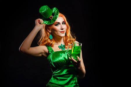 Red hair girl in Saint Patrick's Day leprechaun party hat having fun, holding a mug of ale Foto de archivo