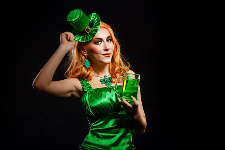 Red hair girl in Saint Patrick's Day leprechaun party hat having fun, holding a mug of ale Standard-Bild
