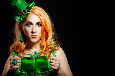 female leprechaun: Red hair girl in Saint Patricks Day leprechaun party hat having fun, holding a mug of ale Stock Photo