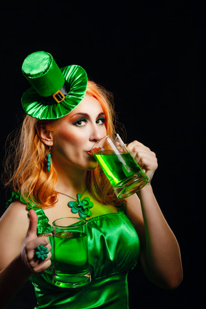 Red hair girl in Saint Patricks Day leprechaun party hat having fun, holding a mug of ale photo