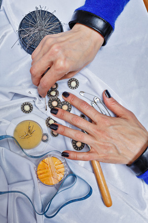 needlewoman: Hands designer clothes at work close-up shot, a woman is not recognizable
