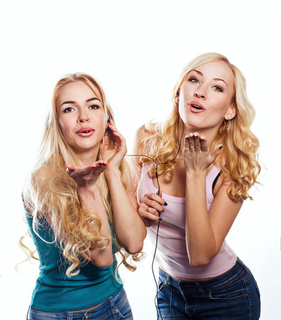 Beautiful girls sisters headphones listening to music with fluttering hair photo