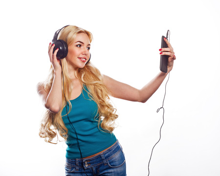 Beautiful female in headphones listening to the music with fluttering hair photo