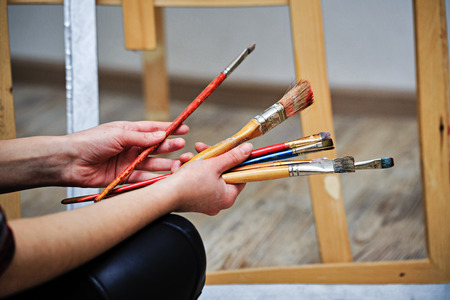 unrecognizable people: The artist holds in her hands a brush. Unrecognizable people Stock Photo