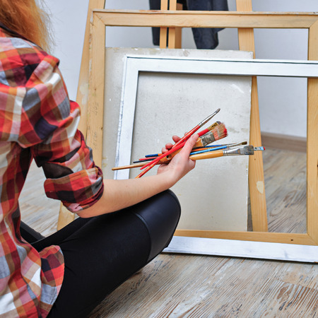 The artist holds in her hands a brush. Unrecognizable people photo