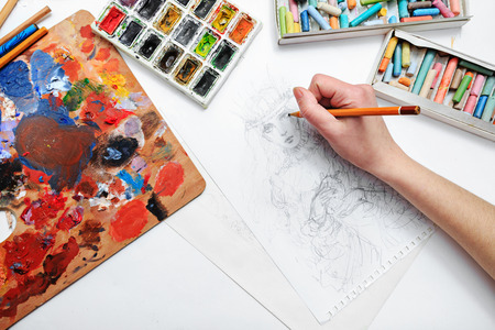 The artist's hand drawing a pencil sketch picture on paper