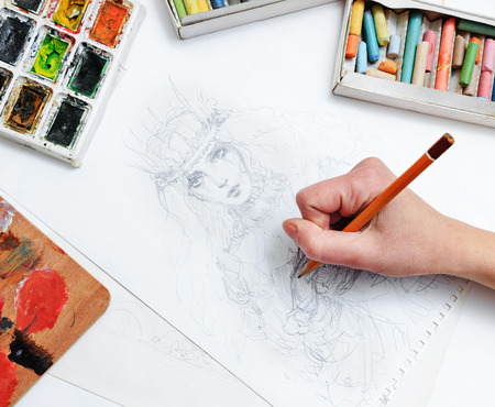 The artists hand drawing a pencil sketch picture on paper photo