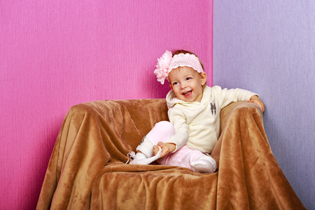 face shot: Little girl sitting in chair with a happy look on her face shot in home interior