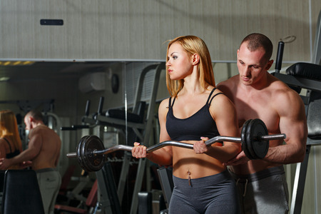 Coach with a client in the gym. Sports Man and athletic girl engaged in fitness in the gym. Trained with a barbell