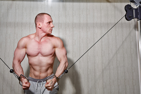 Man trains biceps and triceps in the gym on the simulator photo