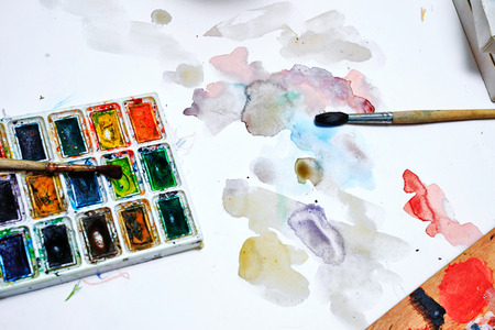 Professional watercolor paints and brushes on a paper background with stains. Concept art background. photo