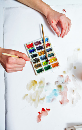 The artists hand drawing a water color on paper. photo