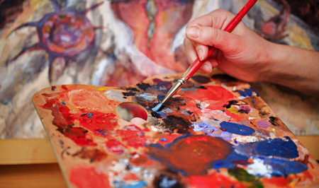paint colorful: Artist brush mix color oil painting on palette is holding in his hand closeup