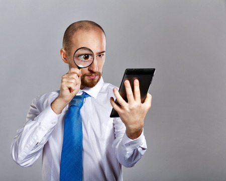 Businessman in shirt and tie looking through a magnifying glass on a tablet PC. Business people. Concept of success.