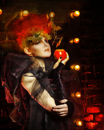 all saints day: Halloween witch with an unusual makeup and headdress of bats holding an apple. Concept for holiday All Saints Day.