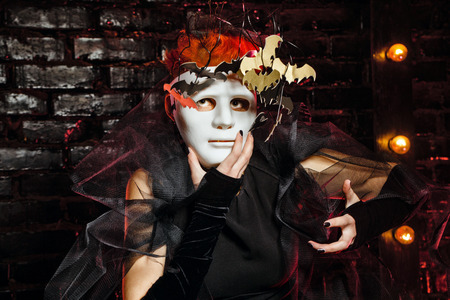 necromancy: Halloween witch with an unusual makeup and headdress of bats holding a mask. Concept for holiday All Saints Day.