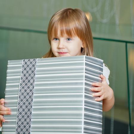 Little cute girl in a beautiful dress holding gift, closeup shot. photo
