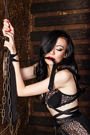Young attractive girl in bra and lace underwear. Girl hands handcuffed with chains. Girl holds in mouth mans tie. The concept of BDSM and bondage.