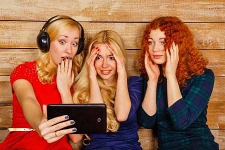 Three sisters, blond and red, listening to music on headphones. Girls are very surprised, looking at screen the tablet PC, making fun selfie. Sisters sitting in the bedroom. photo