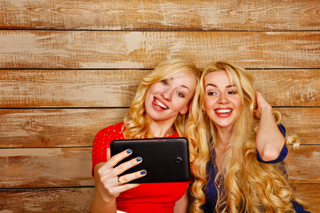 Young sisters with long blonde hair, make selfie on the tablet PC. Girl smiling and showing positive emotions. The concept of youth and technology. photo
