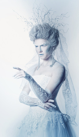 Mysterious and unusual girl with face art in the form of the Snow Queen. Girl dressed in a white dress and has a high hairstyle. Fairy indicates somewhere forefinger. The concept of the kingdom of cold. photo