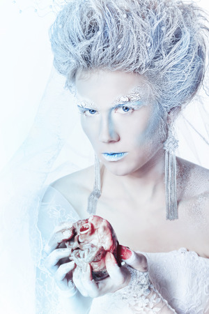 Mysterious and unusual girl with face art in the form of the Snow Queen. Girl holding a human heart in the blood. Bloodthirsty girl looking at the camera. The concept of eternal winter. photo