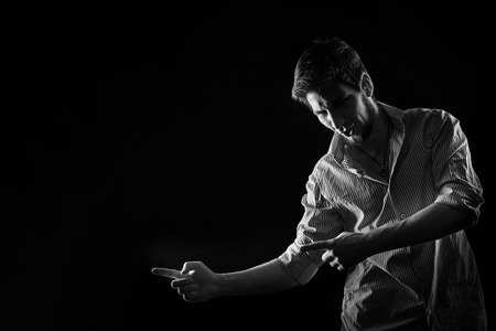 Dramatic portrait of a young man in shirt and jeans, shot in the studio in black and white style. Low key. A man shows his index fingers in motion. Space for text. Stock Photo