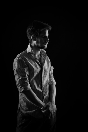 scruple: Dramatic portrait of a young shy man in shirt and jeans, shot in the studio in black and white style