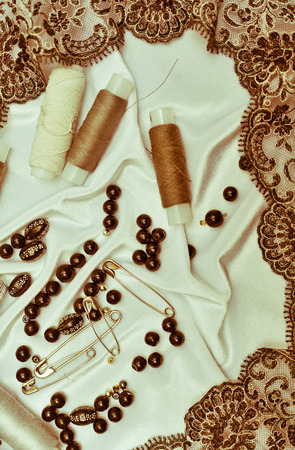 The concept of needlework. Pins, thread, thimbles and pearls lie on a fabric background. photo