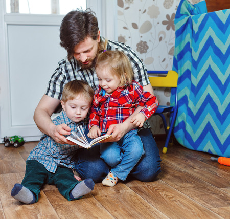 Father and children, brother and sister, reading a book sitting on the floor in the nursery. The concept of child domestic preschool education.