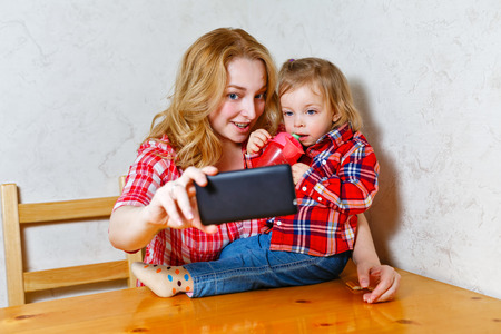 Happy woman and child taking a selfie. Sitting in the kitchen. Happy family. Mother holding a cell phone. Happy motherhood. photo