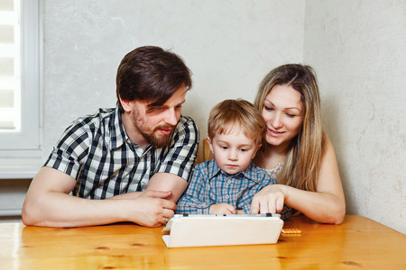 web surfing: Young family. Mother, father and son looking at a tablet pc while sitting at the kitchen table. Web surfing. Happy childhood.