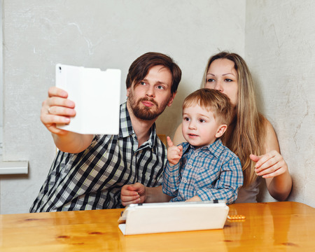 web surfing: Young family. Mother, father and son are doing selfie sitting at the kitchen table. Web surfing. Happy childhood.