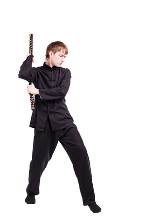The man in a kimono practicing kung fu. The wizard displays a nunchaku kata. Fighter isolated on white background. Concept of healthy life and martial arts.
