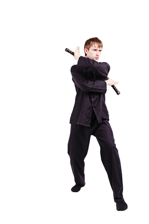 nunchaku: The man in a kimono practicing kung fu. The wizard displays a nunchaku kata. Fighter isolated on white background. Concept of healthy life and martial arts.