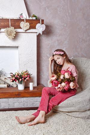 ragazze a piedi nudi: Bella ragazza teenager con un mazzo di fiori primaverili in home interior. Ragazza a piedi nudi seduta su una sedia. Il concetto di un'infanzia felice.