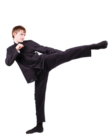 The man in a kimono practicing kung fu. Master rack side kick. Fighter isolated on white background. Concept of healthy life and martial arts. Stock Photo