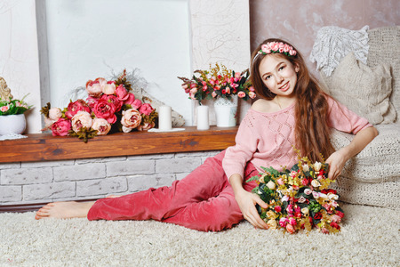 barefoot teens: Beautiful teen girl with a bouquet of spring flowers in home interior. Barefoot girl sitting on the floor. The concept of a happy childhood.