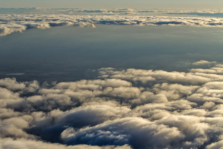 View of clouds from the window of a jet aircraft. Flying above the clouds. Clouds at sunset. Concept travel. photo