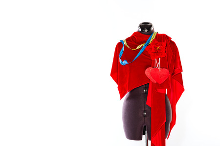 dress form: Mannequin with a piece of red cloth and a measuring tape, a flower and a heart from a fabric. The concept of fashion and fashion design.