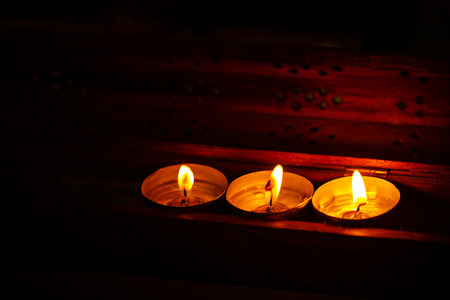 Three candles on a dark background in a warm light. The concept of religious feelings.