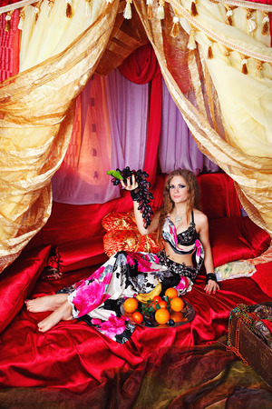 harem: Oriental beauty sit on cushions in her tent and holding a grape. The concept of the Arab harem. Stock Photo