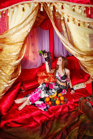 arabian harem: Oriental beauty sit on cushions in her tent and holding a grape. The concept of the Arab harem. Stock Photo