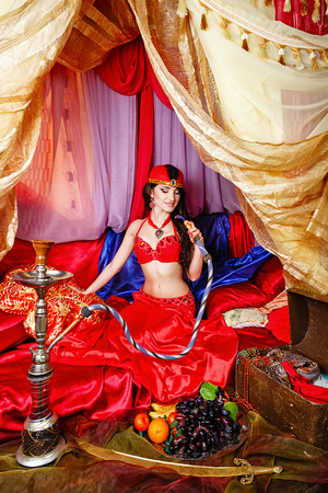 harem: Oriental beauty is sitting in the tent, smoking a hookah. The concept of the Arab harem.