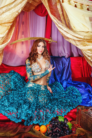 harem: Oriental beauty sitting in a tent and holding a sword on her head. The concept of the Arab harem.